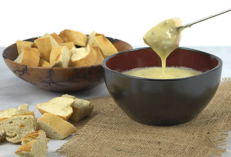 Dripping fork of bread with cheese fondue