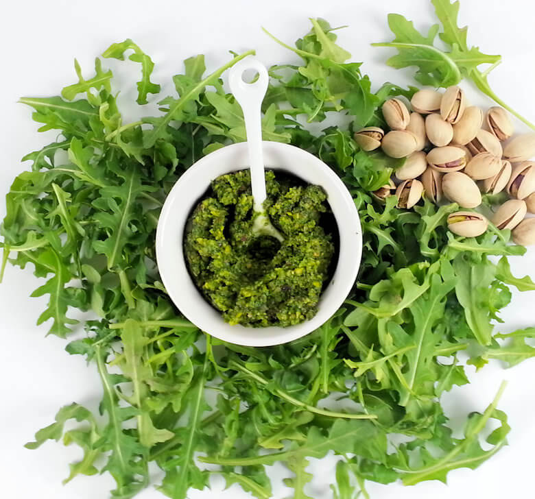 Picture of small bowl of pesto with raw arugula and pistachio nuts