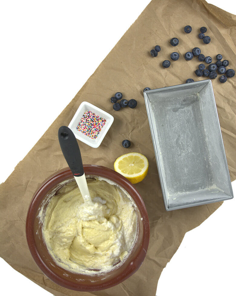 Picture of ingredients, batter, loaf pan, lemon, blueberries, sprinkles