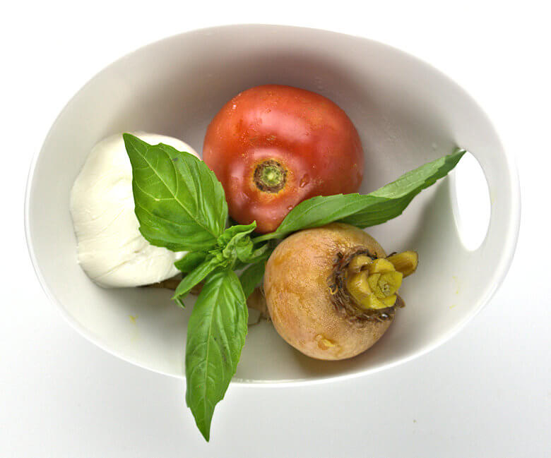 Picture of a bowl with a tomato, beet, mozzarella and basil