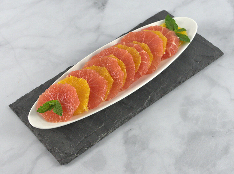 Slices of grapefruit and oranges decorated on a white dish