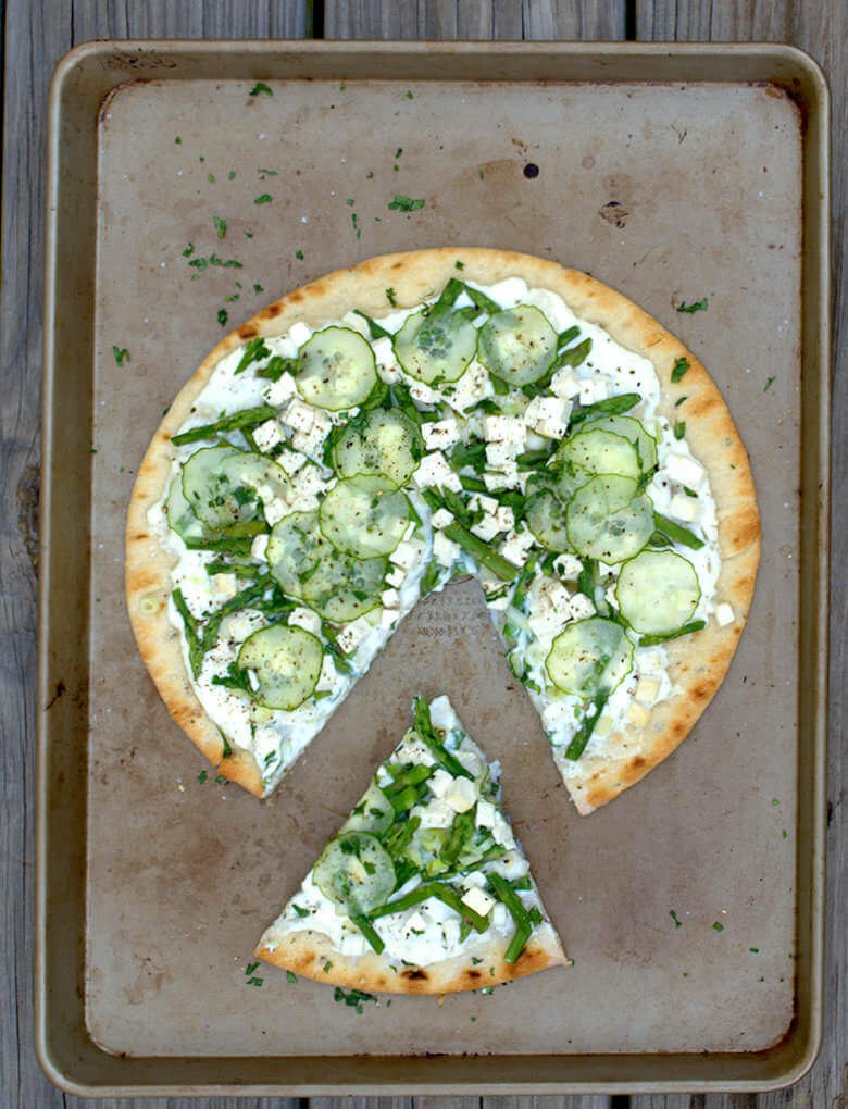 Top down picture of Green Garden Pizza with Ricotta and Tofu, with cut out wedge