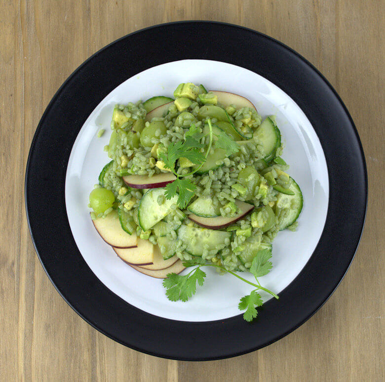Top down picture of a plate with Green Rice Salad with Avocado Grapes and Cucumber