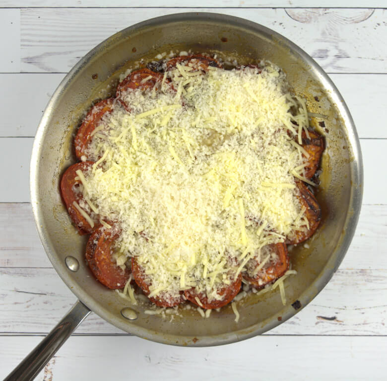 Cooked Roma tomatoes sprinkled with cheese.
